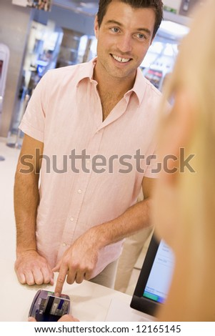 Man entering security details for credit card transaction in store - stock photo