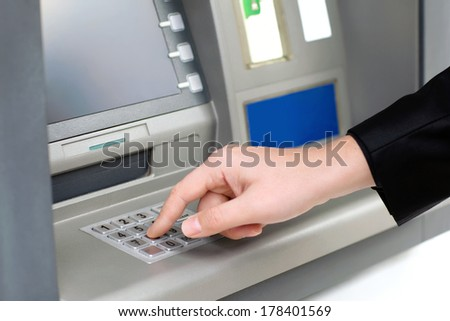 man enters a PIN code and withdraws money from an ATM - stock photo
