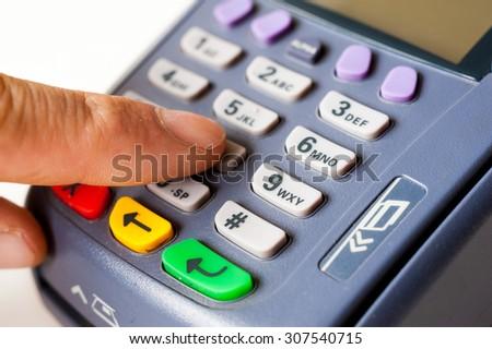 Man enters a PIN code on POS terminal - stock photo