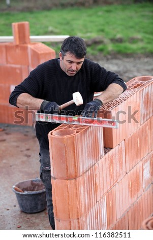 man erecting a brick wall - stock photo