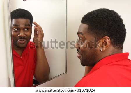 Man examining himself in bathroom mirror