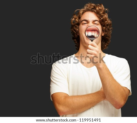 Man Examining His Teeth With Magnifier On Black Background - stock photo