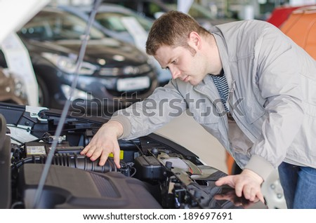 Man examining new car at the dealership. - stock photo