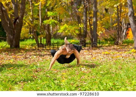 Man exercises yoga in the autumn forest - stock photo