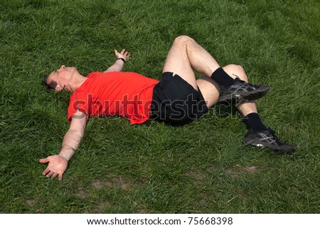 Man exercising and stretching on the grass