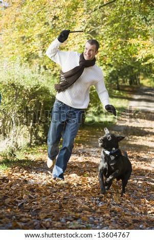 Man exercising dog in autumn woodland - stock photo