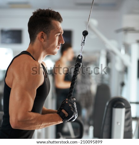 man exercising in trainer for triceps muscles in the gym - stock photo