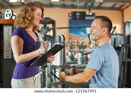 Man exercising on cable machine in gym and listening to female fitness trainer - stock photo