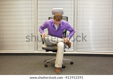 man exercising on chair in office, healthy lifestyle - front  - stock photo