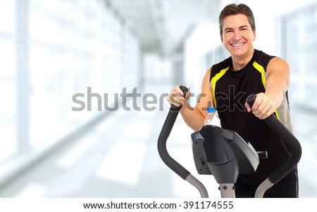 Man exercising on elliptical trainer. - stock photo