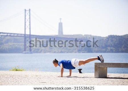 Man exercising with push ups at Lisbon, next to the river - stock photo