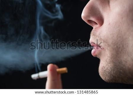 Man exhaling cigarette smoke on black background - stock photo