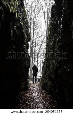 Man exiting from dark cave - stock photo