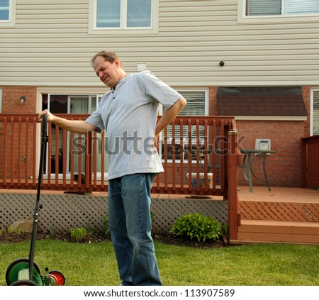 man experiencing backache while working around home - stock photo