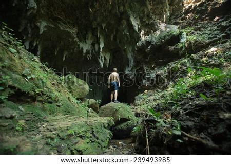 Man exploring remote limestone cave deep in the Rain Forest of Iriomote-jima, Okinawa, Japan - stock photo