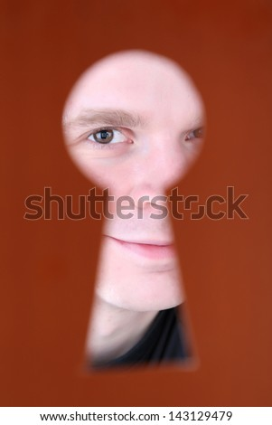 Man eye looking through hole in keyhole, on brown background - stock photo
