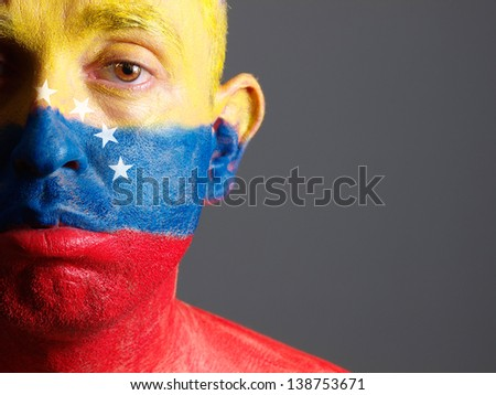 Man face painted with venezuelan flag. The man is sad and photographic composition leaves only half of the face. - stock photo