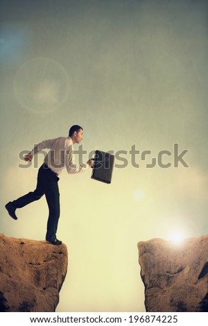 man facing a business challenge makes a leap - stock photo