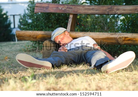 Man fallen down holding a syringe, on the ground next to a bench in the park - stock photo