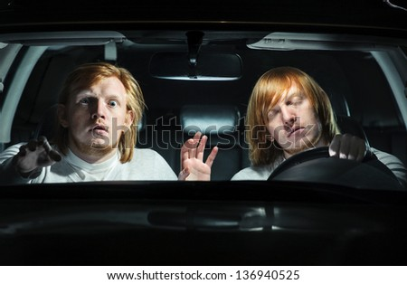 Man falling asleep behind the steering wheel, while his  twin is terrified, trying to warn him of an imminent collision - stock photo