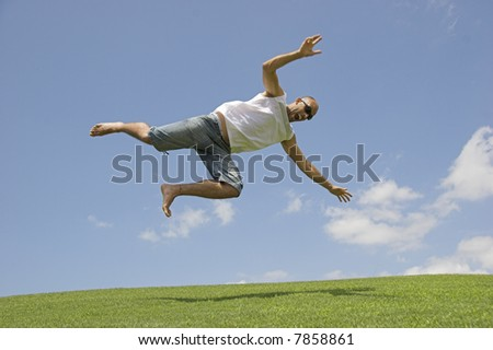 Man falling into the grass of a meadow - stock photo