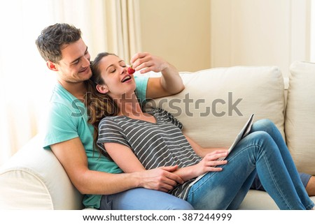 Man feeding a strawberry to woman on sofa - stock photo