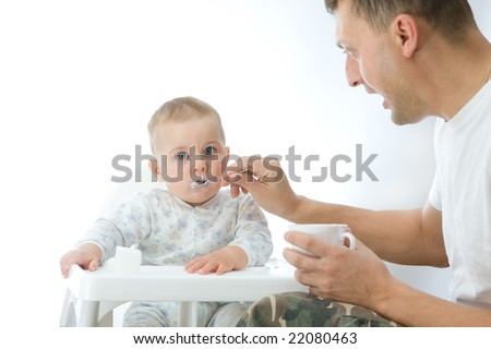 man feeding baby with a spoon, on bright background - stock photo