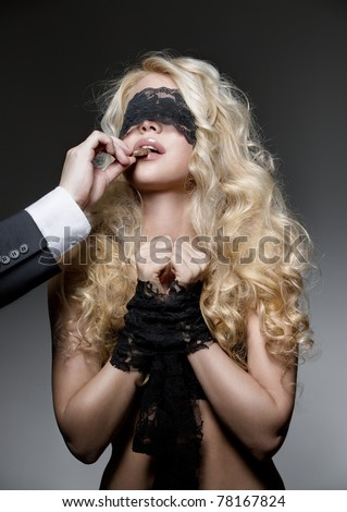 man feeding piece of chocolate to gorgeous tied blonde - stock photo