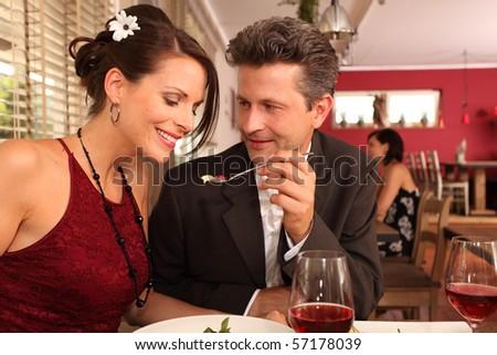 man feeding woman - love couple in a restaurant - stock photo