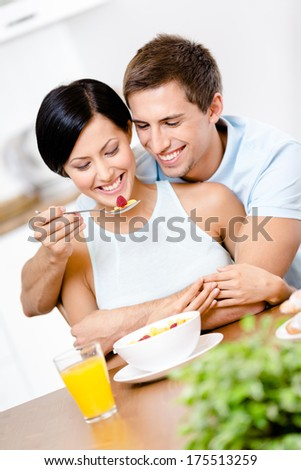 Man feeds and hugs his girlfriend sitting at the kitchen table. Concept of healthy and dieting food - stock photo