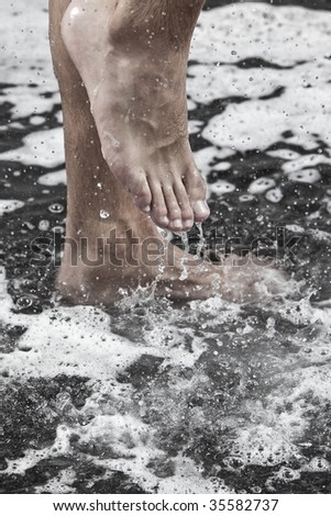 man feet in the shower under the streams of water - stock photo