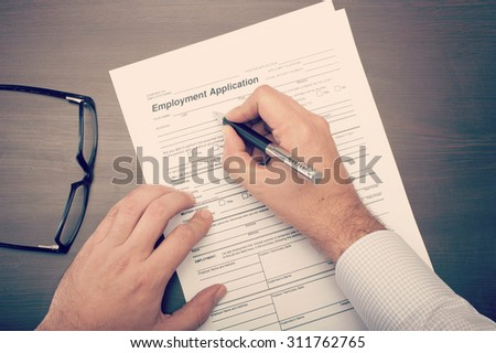 Man filling a job application form viewed from above