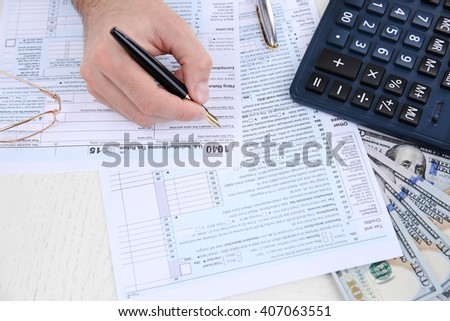 Man filling American form of Individual Income Tax Return at the table - stock photo