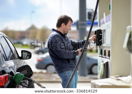 Man filling gasoline fuel in car holding nozzle - stock photo