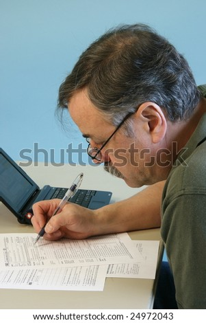 Man Filling in 1040 Federal Income Tax Form - stock photo