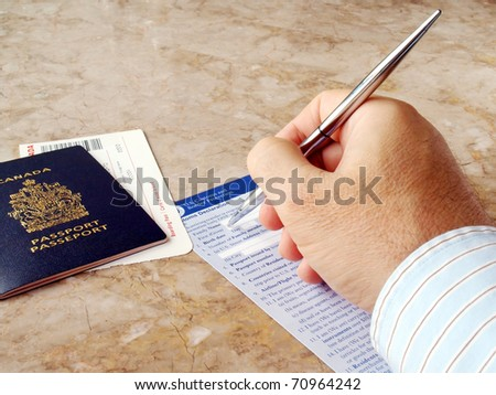 Man filling out U.S. customs and border form with Canadian Passport - stock photo