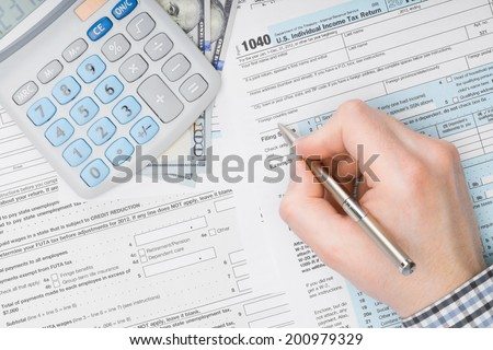 Man filling out 1040 US Tax Form - view from top - stock photo