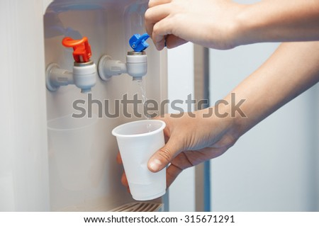 Man filling plastic cup at water cooler - stock photo