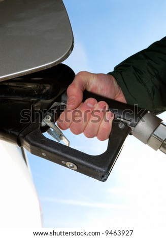 Man filling tank at gas station. Detail of hand holding nozzle. - stock photo