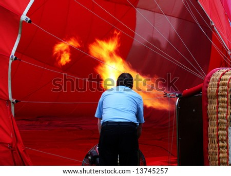 Man fills hot air balloon before take off - stock photo