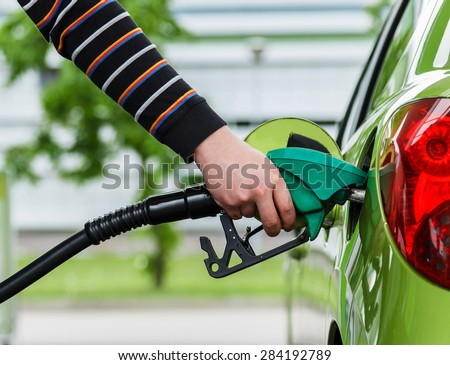 Man fills up his car with a gasoline at gas station - stock photo