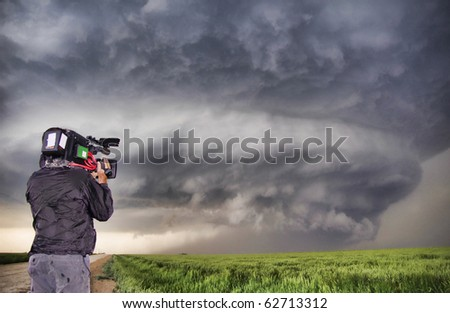 Man filming a supercell thunderstorm in a Kansas field on May 27 2007. - stock photo