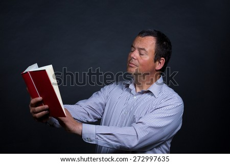Man finding it increasingly difficult to read without glasses - stock photo