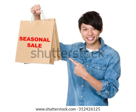 Man finger point to shopping bag for showing phrase of seasonal sale