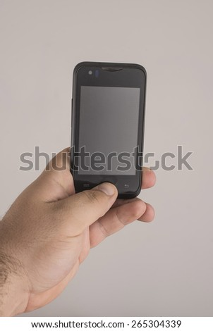man finger Pressing a button on cell mobile phone smartphone, touch empty screen backdrop, clipping path Isolated on gray background  - stock photo