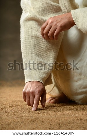MAn finger writing in the sand in close up view - stock photo
