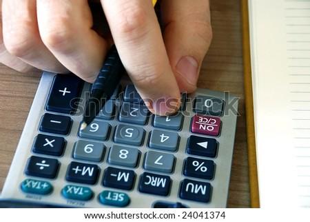 man fingers over gray calculator buttons closeup - stock photo