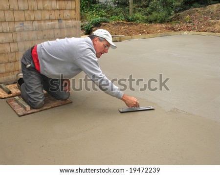 Man finishing concrete slab - stock photo