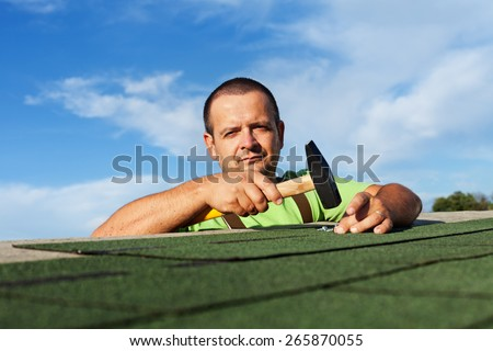 Man finishing installing the bitumen roof shingles - fastening the last pieces with nails and hammer - stock photo