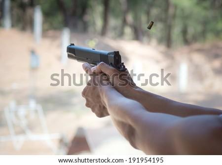 Man firing pistol at firing range - stock photo